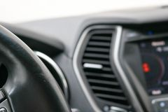 The angle of the leather black steering wheel in the car. On the background of the dashboard Stock Image