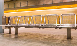 Yellow Train speeding behind metal Seats Royalty Free Stock Photos