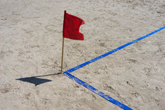 Angle playground on the beach with blue ribbon and red flag Stock Photo