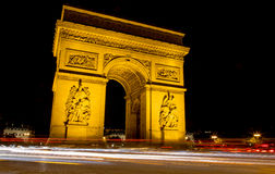 Angle shot of Golden Arc de Triomphe at night. Arc de Triomphe in the subject with car lights in the foreground Stock Photos