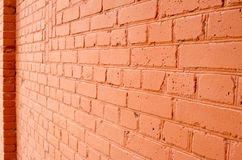Angle view of a brick wall with a layer of red paint. With blurred long-range plan to use as a background Stock Photography