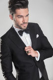 Angle view of an elegant young man ajusting his tuxedo Royalty Free Stock Photos