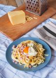 Angle view of pasta with egg, ham, cheese and herbs. Mediterranean supper with cutlery on checked towel. royalty free stock photos