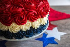 Patriotic Cake in Red White and Blue Rosettes with Stars. Angle view of patriotic cake in red, white and blue rosettes with stars on a wood table top Royalty Free Stock Image
