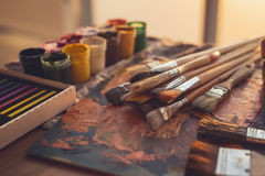 Angle view photo of palette with mixed oil paints, gouache, crayons and paintbrushes set in art studio. Stock Image