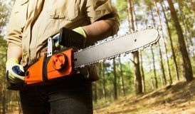 Worker standing with chainsaw angle view. royalty free stock images