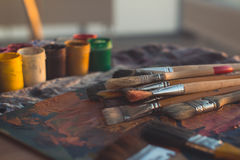 Angle view picture of an old palette with oil paints and gouache set. Clean painter workplace ready for drawing. Royalty Free Stock Images
