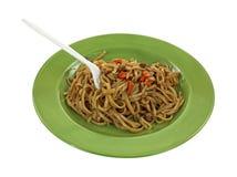 Teriyaki Noodles Fork Green Plate. An angle view of a plate of  prepared teriyaki noodles Royalty Free Stock Image