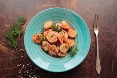 Angle view on a plate with shrimps. Fresh shrimps served on a blue plate with dill Stock Photos