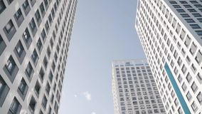 Angle view of white skyscrapers against blue sky. Frame. Fantastic below view stock video footage