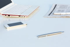 Angle View of Work Place with Laptop Telephone Pen and Business Newspaper Royalty Free Stock Images