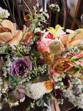 Angled bouquet of colorful pastel flowers spilling over on wood bench. Angled bouquet of colorful pastel flowers spilling over on wood royalty free stock images