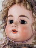Angled close up on cute female doll face stock image