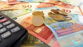 Euro banknotes, coins and calculator royalty free stock photo