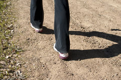 Angled close up of woman's feet hiking in black pants Royalty Free Stock Photos