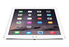 Angled front view of Apple Silver iPad Air 2 with iOS 8 lies on Stock Photography