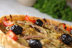 Angled onion and olive pie. Angled view of light and healthy onion, olive and tomato tart, fresh baked on white table cloth Royalty Free Stock Image
