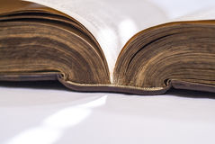 Angled open bible, detailing spine and page edge. An angled shot of an old open book, detailing the spine and page edges Royalty Free Stock Images