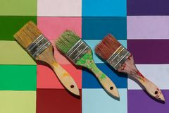 Angled paint brushes on a brightly colored wood tile background. Three angled paint brushes on a brightly colored wood tiled background Royalty Free Stock Photos