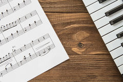 Angled Piano Keyboard On Wooden Background With Notes Stock Photos