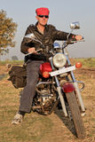 Angled portrait of Bike rider in India. Angled portrait of european bike rider on tour in India int he hinterlands and farmlands of Gujarat royalty free stock images