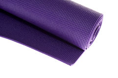 Angled rolled exercise mat. Looking down at rolled up purple yoga or pilates mat Royalty Free Stock Photography