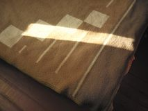 Sunlight across bed. Angled shot of a sunlight across the bed covered with wool blanket royalty free stock image