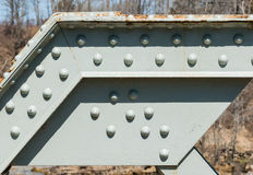 Angled steel girder with rivets on painted surface. Stock Image