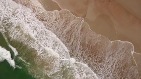 Angled Top Down View of Ocean Surf. 8532 An angled aerial top-down view of the daytime ocean surf hitting against a sandy beach with beachgoers walking along the stock video footage