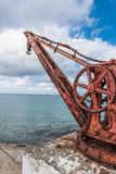 Angled view of Antique red iron boat crane anchored in concrete. Along the shoreline in urban town on St. Croix Stock Photo