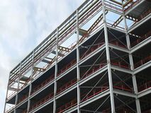 Angled view of a large building development under construction with steel framework and girders supporting the metal floors with b royalty free stock photos