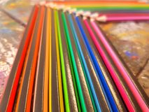 Angled view of pencils laid out in rainbow order on a table with a white background. Angled view pencils laid out rainbow order tablle table white background royalty free stock photography
