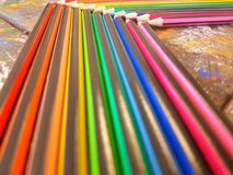 Angled view of pencils laid out in rainbow order on a table with a white background. Angled view pencils laid out rainbow order tablle table white background stock images
