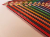 Angled view of pencils laid out in rainbow order on a table with a white background. Angled view pencils laid out rainbow order tablle table white background stock image