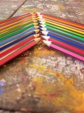 Angled view of pencils laid out in rainbow order on a table with a white background. Angled view pencils laid out rainbow order tablle table white background royalty free stock photo