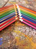 Angled view of pencils laid out in rainbow order on a table with a white background. Angled view pencils laid out rainbow order tablle table white background royalty free stock photos
