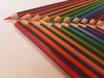 Angled view of pencils laid out in rainbow order on a table with a white background. Angled view pencils laid out rainbow order tablle table white background stock photography
