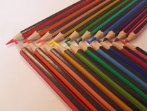 Angled view of pencils laid out in rainbow order on a table with a white background. Angled view pencils laid out rainbow order tablle table white background royalty free stock images