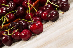 Angled view of Ripe Black Cherries laying in front of basket on Stock Photo