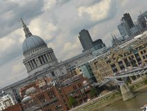Angled View of St Pauls Cathedral London England. Angled City skyline view of  River Thames, Millennium Bridge and St Pauls Cathedral London England Royalty Free Stock Image