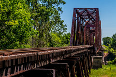 Angled View of a Train Track and Old Iconic Truss Bridge. Angled View of an Old Railroad Trestle with an Old Iconic Iron Truss Bridge Over the Brazos River Royalty Free Stock Image