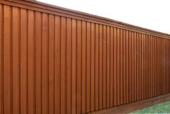 Angled view of a wood fence. Angled view of a stained brown cedar board-on-board fence Stock Photos
