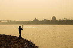 Angler. Twilight, an angler hooked a fish being harvested Royalty Free Stock Images