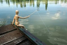The angler. A puppet fishing on the bank of a river royalty free stock photo