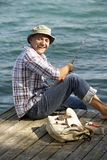 Angler. Laughing fisherman on a wooden pier royalty free stock images