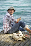 Angler. Man fishing from a wooden pier royalty free stock images