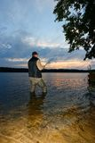 Angler. Catching the fish during cloudy sunrise stock photo