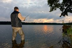 Angler. Catching the fish during cloudy sunrise royalty free stock photography