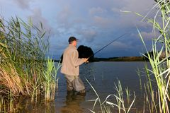 Angler. Catching the fish during stormy weather stock image