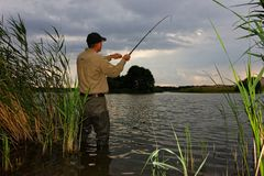 Angler. Catching the fish during stormy weather royalty free stock photos